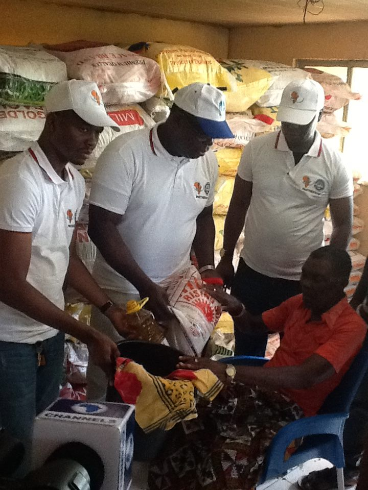 Dr Chris Ekiyor, Dr George Uzowanne and Hon Kelly Penawei jointly presenting food items to an elderly man from Oporoza community