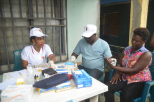 Labouratory scientist taking blood sample from a patient